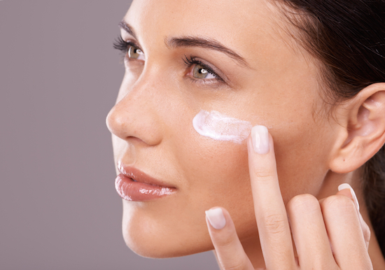 Woman applying moisturiser should you wear sunscreen during winter by Healthist.com