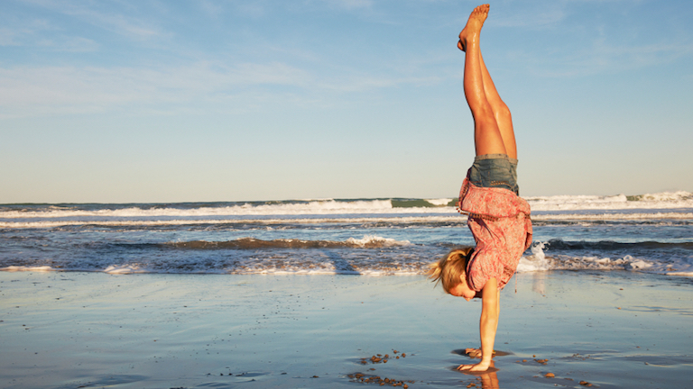 Woman doing handstand at the beach, Expert tip of the week with Genny Wilkinson-Priest, by Healthista.com