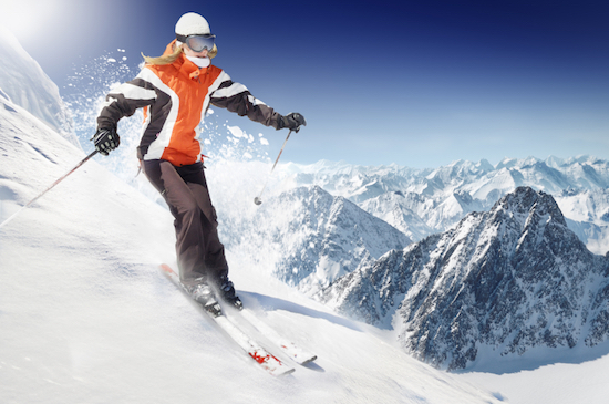Woman skiing in the mountains, should you wear sunscreen during winter, by Healthista.com
