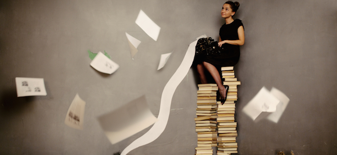 Woman sitting on pile of book, 8 weeks to achieving your goals blog: Week 6 and journalist Alice Hart-Davis learned that accepting changes is easier than fighting them, by Healthista.com