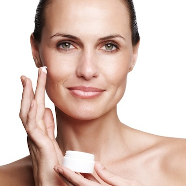 Lady holding moisturising cream and applying to her face, What does hydration and moisturisation do for our skin?, by Healthista.com