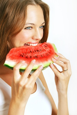 Woman eating slice of watermelon, what to eat for great skin, by healthista