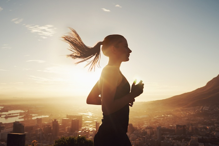 Woman running at sunset, 7 ways to boost your brain performance, by healthista.com
