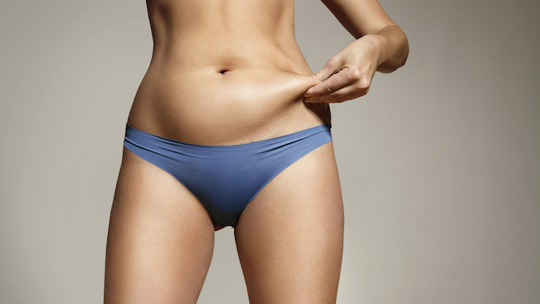 woman pinching fat on tummy, why diets make us fat, by healthista