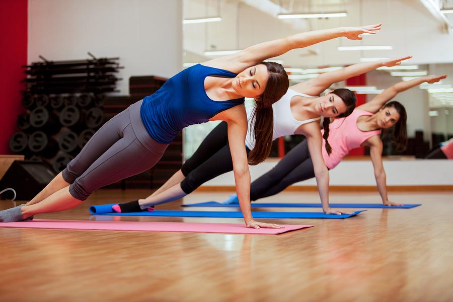 Side plank yoga pose by three women