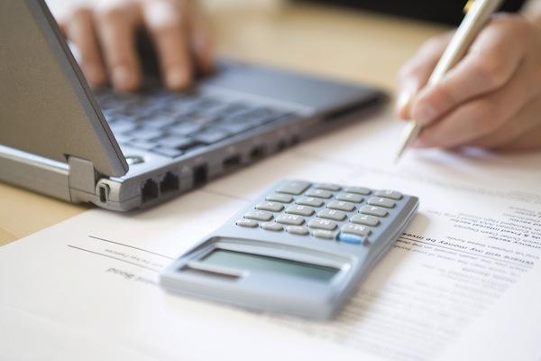 Cropped image of woman's hands calculating home finances at desk
