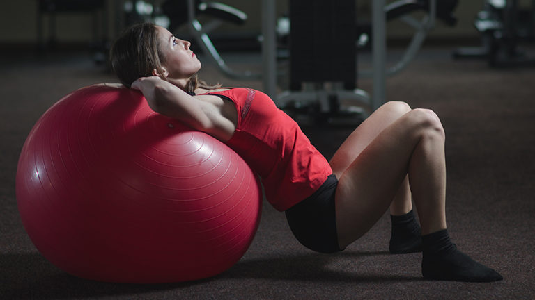 woman-on-exercise-ball-how-to-sync-your-workout-to-your-cycle-healthist