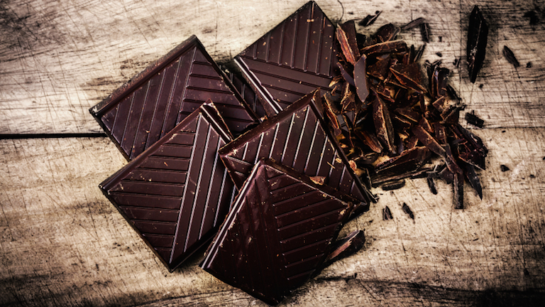 Chopped Chocolate Bar on wooden background closeup. Broken dark chocolate bar on wood table