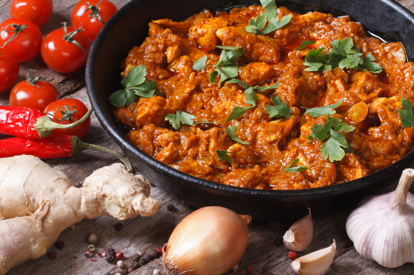 Chicken in curry sauce in a pan with the ingredients