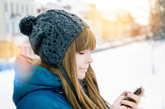 Girl looking at phone, should you wear sunscreen during winter, by Healthista.com