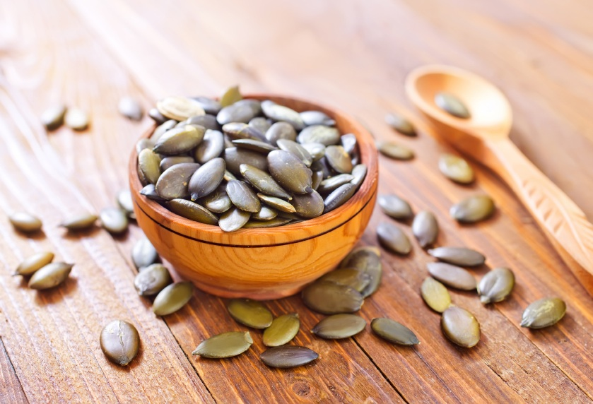 pumpkin seeds in a bowl and over wooden table, 5 healthy dishes under a fiver, by Healthista.com