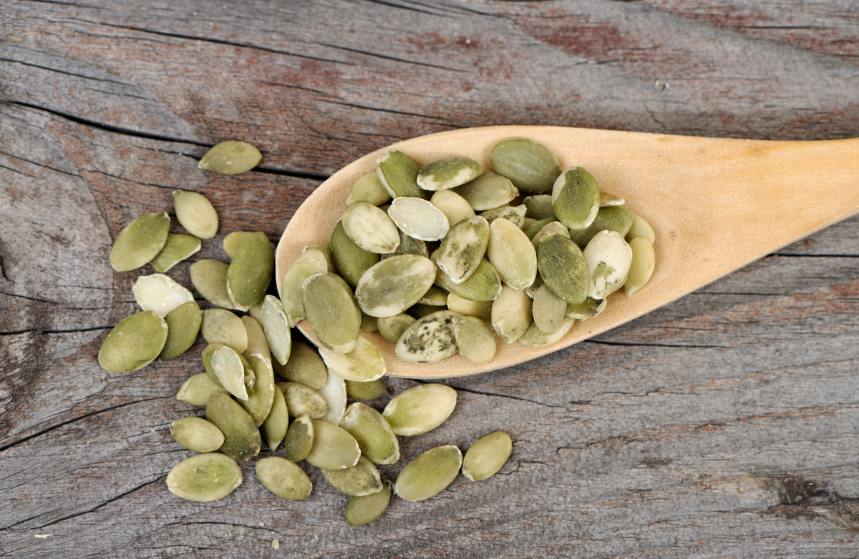 pumpkin seeds in wooden spoon, grocery list to help fight fatigue by healthista.com