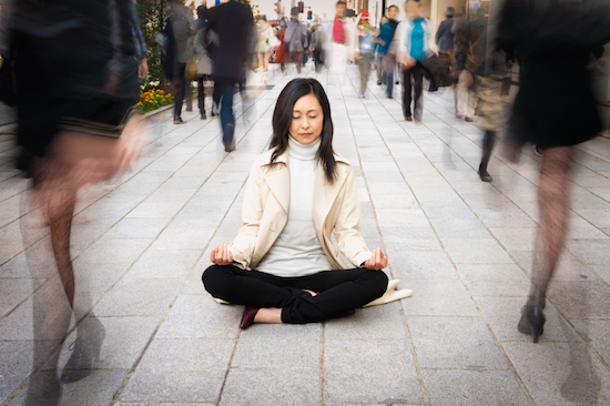 woman meditating on the street