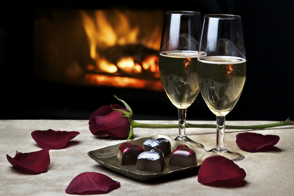 Two champagne glasses with roses, chocolate and fire in background, Why alcohol may be the best thing for your fertility, by Healthista.com