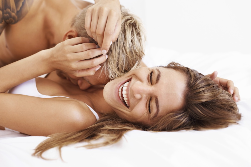 Laughing couple on bed, Why alcohol may be the best thing for your fertility, by Healthista.com