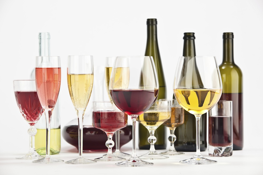 red and white wine glasses and bottles half full of alcohol, Why alcohol may be the best thing for your fertility, by Healthista.com