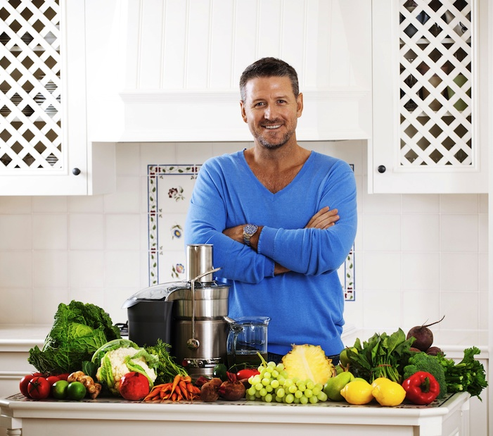 Joe Cross in kitchen with fruit, veg & jucer infront of him, Tips for a healthy juice cleanse & how to remain healthy afterwards, by Healthista.com
