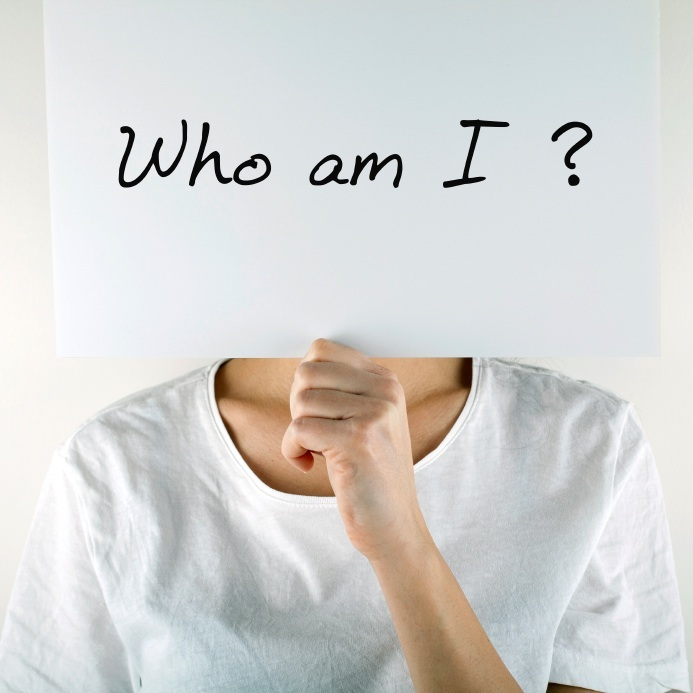 Woman holding piece of paper infront of face with 'Who am I?' written on it, 6 signs that you're an outsider, by Healthista.com