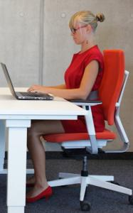 woman in office chair whats really causing your lower back pain by Healthista.com