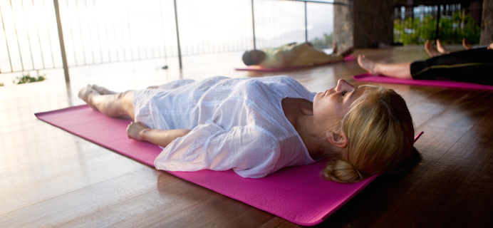 laying-on-yoga-mat-learn-yoga-online-by-Healthista.com