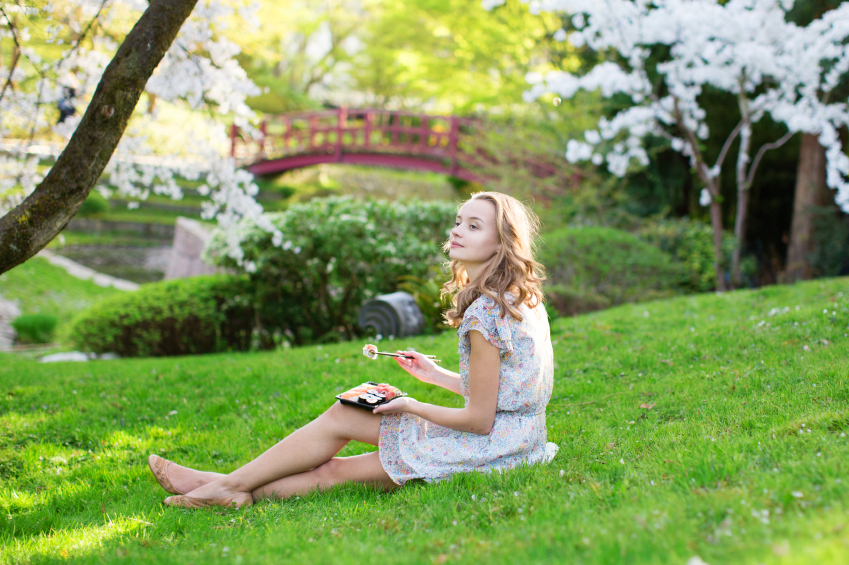 woman-in-garden-eating-sushi-balance-your-gut-by-Healthista.com