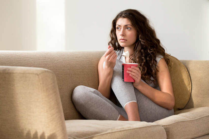 Woman eating on sofa, Emotional eating HOW, by healthista.com