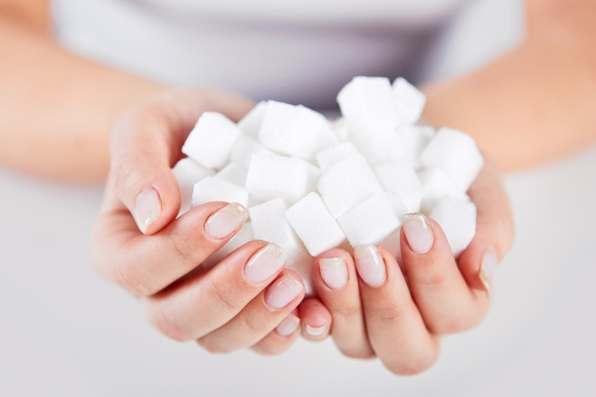 Woman holds in hands of sugar cubes, ways to avoid sugar, by healthista.com