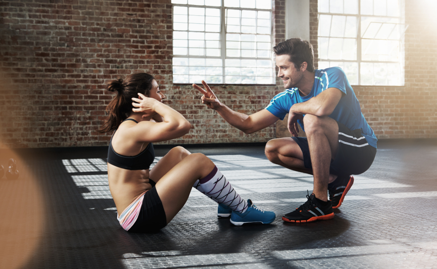 woman doing sit-ups with her trainer, how much exercise do we need to do to lose weight?