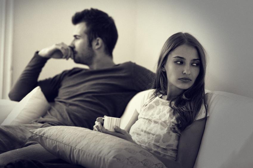 Couple sitting on sofa, relatioship problems, by healthista