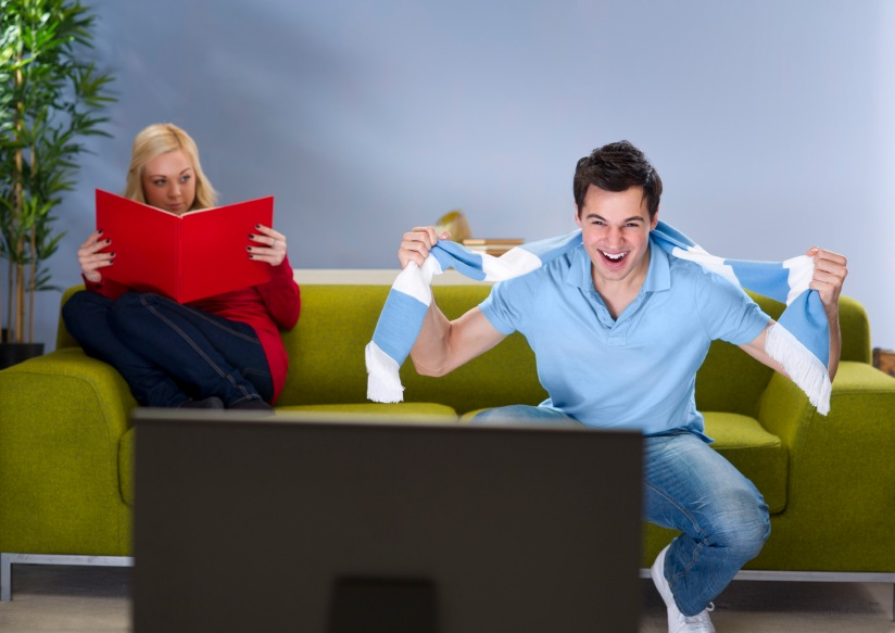 boyfriend watching football as girlfriend disapproves, relationship problems, by healthista