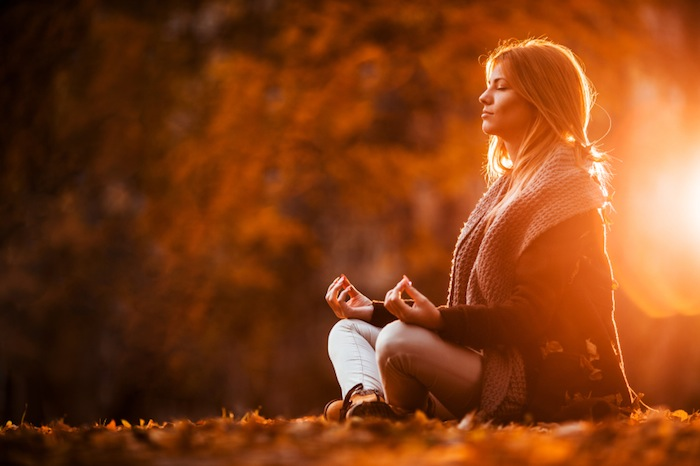 Woman meditating in autumn day, 7 ways to boost your brain performance, by healthista