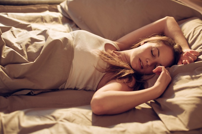Woman sleeping in bed, 7 ways to boost your brain performance, by healthista