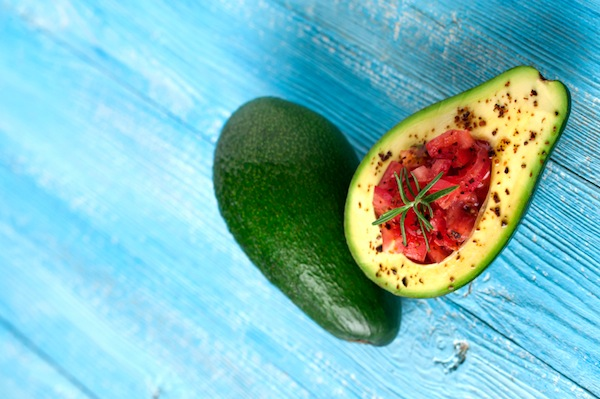 avocado on blue wooden background, 11 reasons you're always hungry, by healthista
