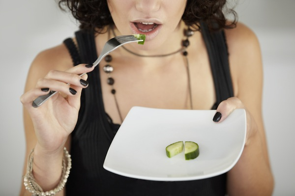 A young woman eating only one piece of cucumber for lunch, 11 reasons why you're always hungry, by healthista