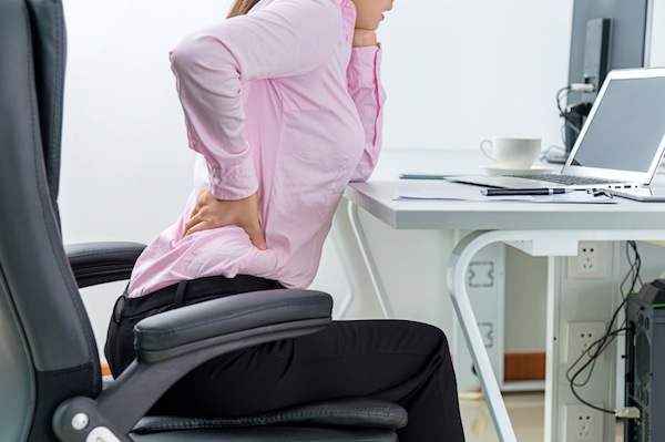 woman rubbing back at work desk, 7 ways to get rid of back pain, by healthista