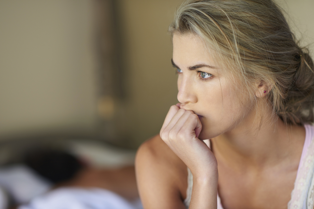 Shot of a young woman deep in thought while her husband sleeps in the background
