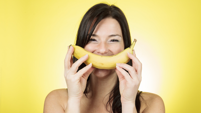 woman-holding-a-banana-as-a-smile-foods-that-look-like-the-body-part-theyre-good-for-by-healthista.
