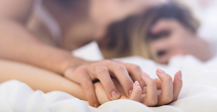 couple-holding-hands-in-bed-sex-after-childbirth-by-healthista