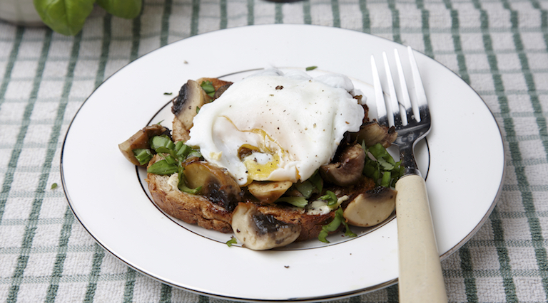Poached egg over herby mushrooms on toast