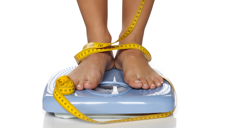 woman-standing-on-scales-with-tape-wrapped-round-her-feet-why-diets-make-us-fat-by-healthista