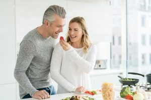 Happy couple cooking together at home and looking very playful - healthy eating concepts