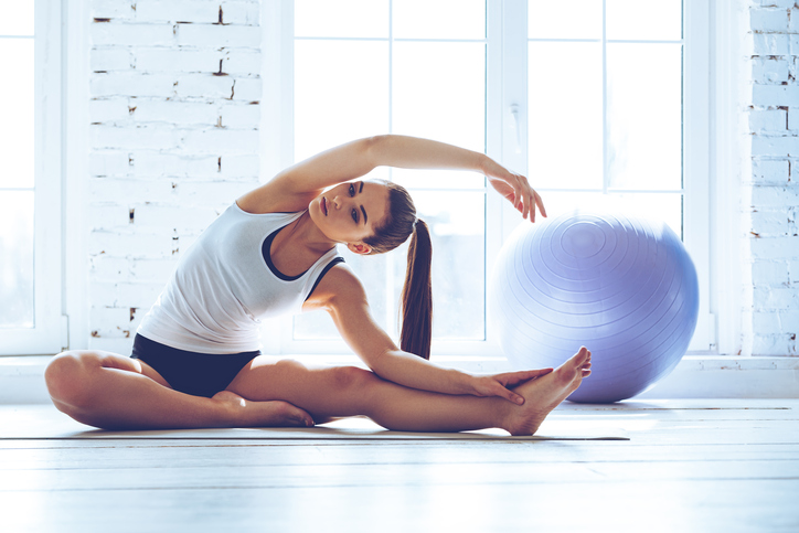 woman doing yoga, how to keep your new year's resolutions by healthista