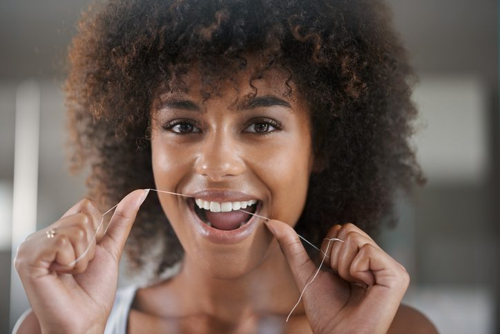 woman flossing 6 things your dentist wishes you would do Healthista