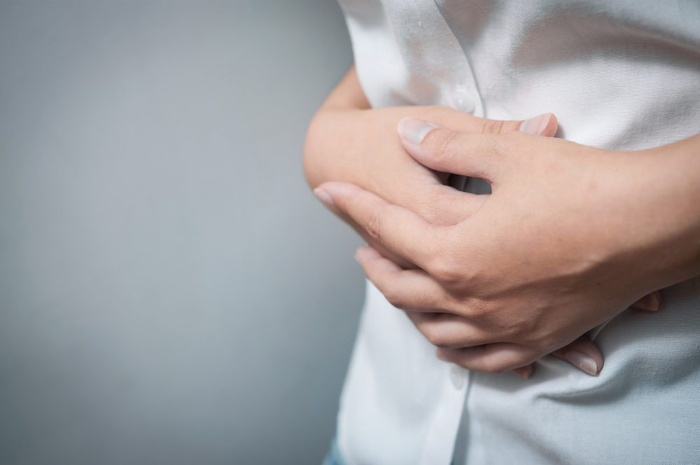 woman folding hands over stomach Why sex hurts - the gynaecologist's guide Healthista