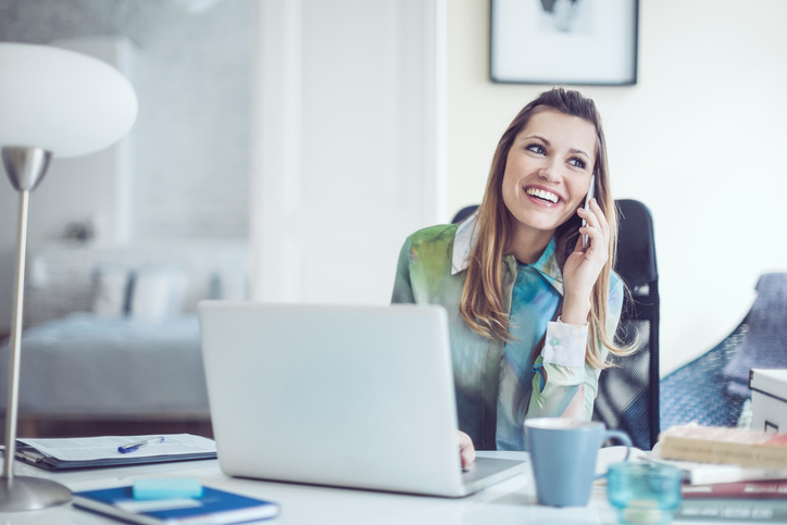 woman smiling on the phone, 8 best ways to be the most powerful version of you on International Women's Day by healthista