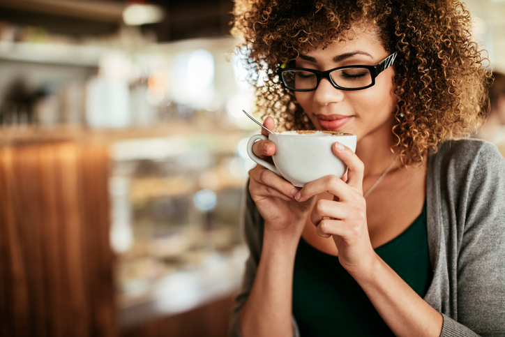 woman happy with coffee, 5 pitfalls of coffee by healthista