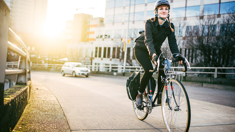 woman-riding-bike-past-building-cycle-plan-made-easy-by-healthista.com-main.jpg