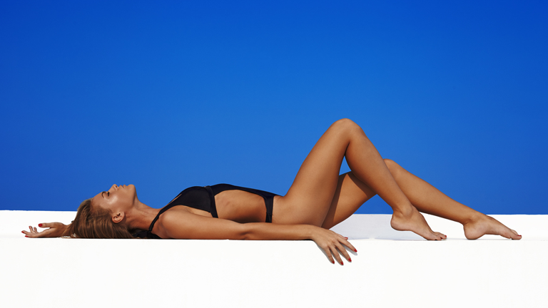 woman lying down with a tan, best fake tans with natural ingredients by healthista