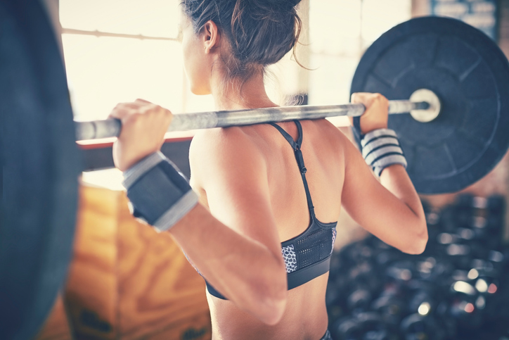 Rear view of woman exercising with barbell in gym Is less more when it comes to exercise? 5 signs of overtraining by healthista.com