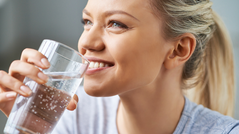 woman drinking water, 'It burns when I pee, what now? The GP's guide by healthista.com